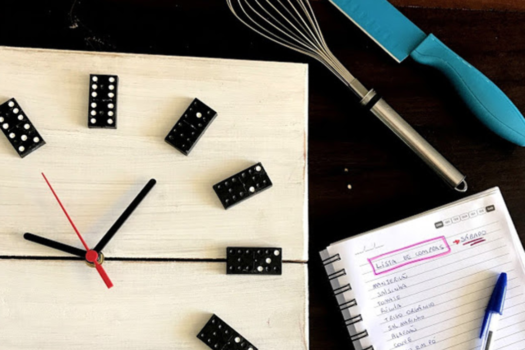 utensílios de cozinha, um caderno e um relógio