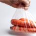 mão segurando um saco de cenouras