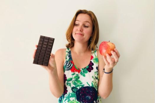eu segurando chocolate em uma mão e maçã na outra