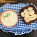 uma cesta com um potê de biscoito de arroz e um pote com patê de feijão
